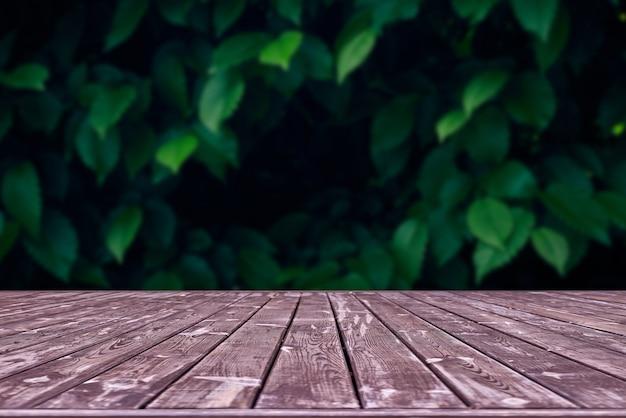 Макет. пустой деревянный стол палуба с листвой боке пространства. Premium Фотографии
