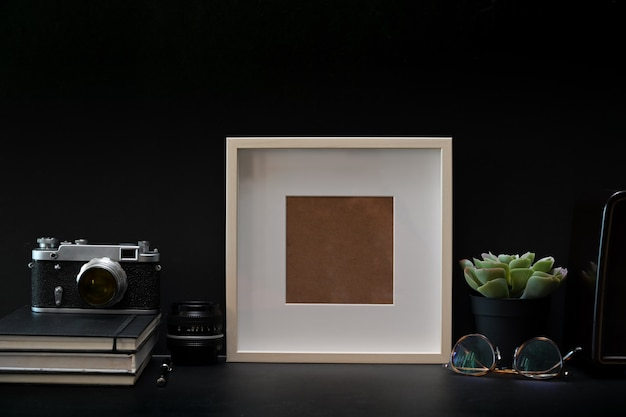 Mockup frame photo poster with books and vintage camera on dark table Premium Photo
