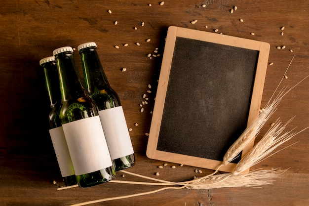 Mockup of green bottles of beer with blackboard on wooden table Free Photo