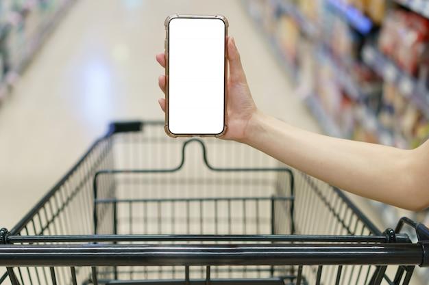 Макет, руки держат пустой белый экран мобильного телефона с тележкой в супермаркете Premium Фотографии