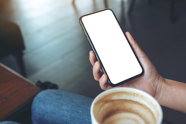 Макет изображения руки, держащей черный мобильный телефон с пустым экраном во время питья кофе в кафе Premium Фотографии