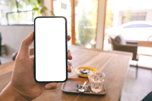 Мокап изображения мужской руки, держащей и показывающей черный мобильный телефон с пустым белым экраном, сидя в кафе Premium Фотографии