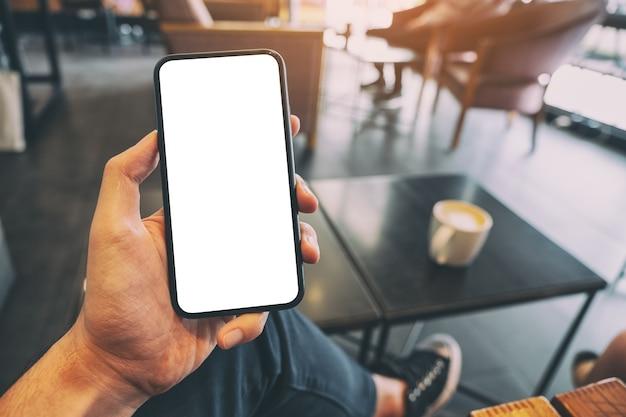 Мокап изображения мужской руки, держащей черный мобильный телефон с пустым экраном с чашкой кофе на столе в кафе Premium Фотографии
