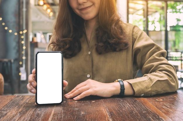 Макет изображения женщины, держащей и показывающей черный мобильный телефон с пустым белым экраном на столе в кафе Premium Фотографии