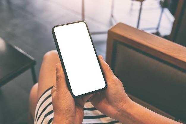 Макет изображения женщины, держащей черный мобильный телефон с пустым белым экраном в кафе Premium Фотографии