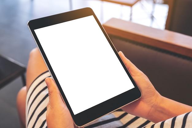 Макет изображения женщины, сидящей и держащей черный планшетный пк с пустым белым экраном рабочего стола Premium Фотографии