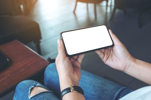 Макет изображения рук женщины, держащей черный мобильный телефон с пустым белым экраном по горизонтали в кафе Premium Фотографии