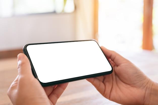 Макет изображения женских рук, держащих черный мобильный телефон с пустым белым экраном по горизонтали на деревянном столе Premium Фотографии
