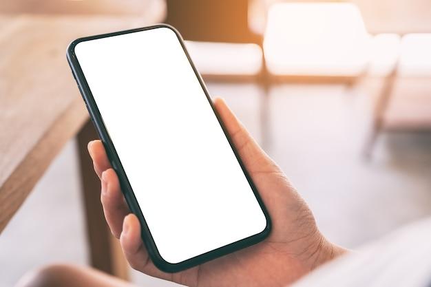 Макет изображения женских рук, держащих черный мобильный телефон с пустым белым экраном в кафе Premium Фотографии