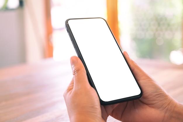 Макет изображения женских рук, держащих черный мобильный телефон с пустым белым экраном на деревянном столе Premium Фотографии