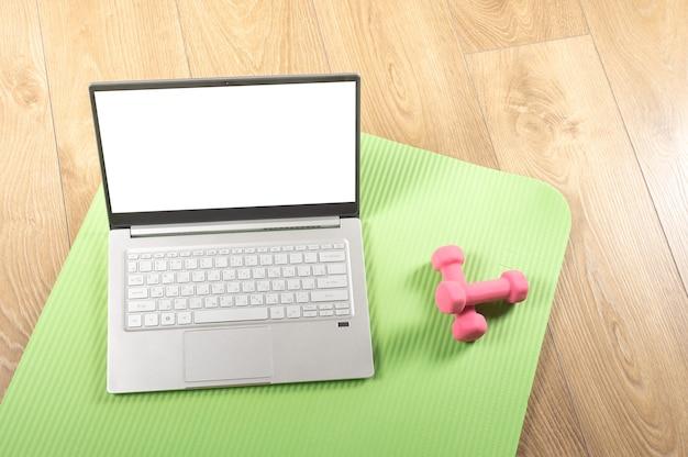 Изображение мокапа спортивные онлайн-тренировки в домашнем тренажерном зале с использованием компьютера или телефона и спортивных аксессуаров Premium Фотографии