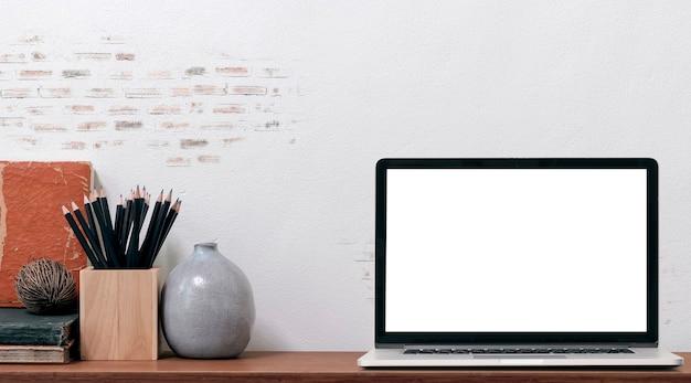 빈 화면 및 나무 테이블과 오래 된 벽돌 벽, 복사 공간에 공급 모형 노트북 컴퓨터. 프리미엄 사진
