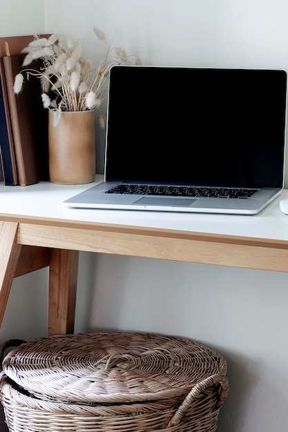 Mockup laptop with black screen on wooden table. Premium Photo
