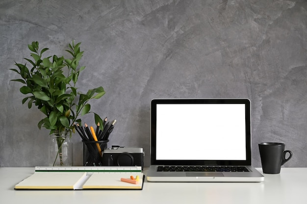Mockup laptop on workspace with office supplies and loft wall Premium Photo