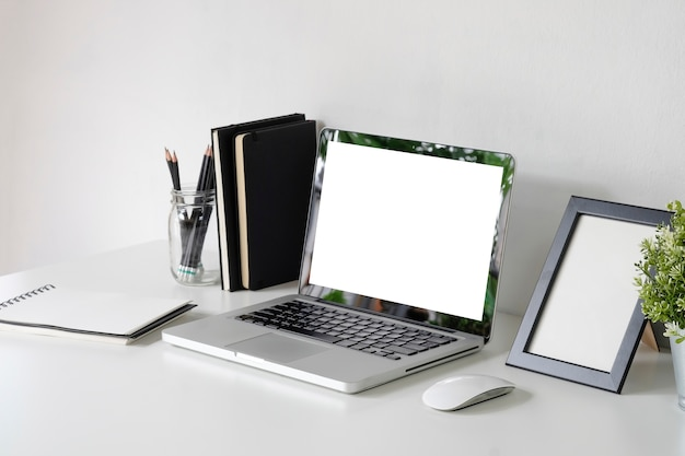 Mockup laptop on workspace with photo frame, jar of pencil, mouse on office table. Premium Photo