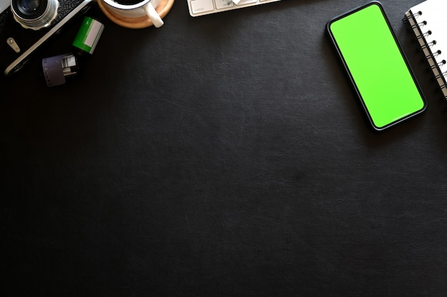 Mockup mobile phone on photographer workplace with leather dark background Premium Photo