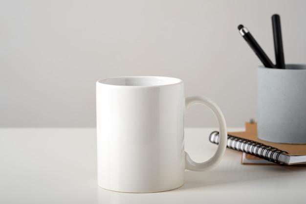 미니멀 한 인테리어, 비즈니스 문구 및 메모장의 테이블에 흰색 머그잔의 모형. 프리미엄 사진