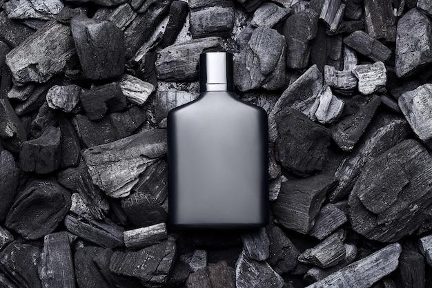어두운 석탄 배경에 검은 향수 향수 병 모형의 모형. 평면도. 수평 프리미엄 사진