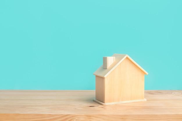 나무 테이블 배경에 파란색 파스텔 색상으로 나무로 만든 집의 모형 프리미엄 사진