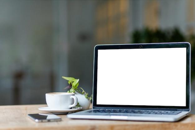 Макет портативного компьютера с пустым экраном с чашкой кофе и смартфоном на столе фона кафе, белый экран Premium Фотографии