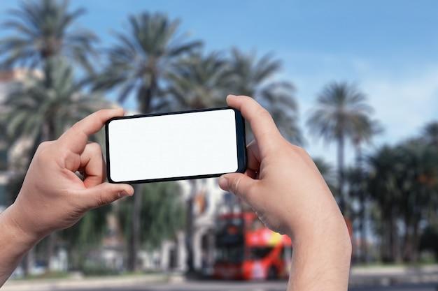 Макет смартфона в мужских руках на улице Premium Фотографии