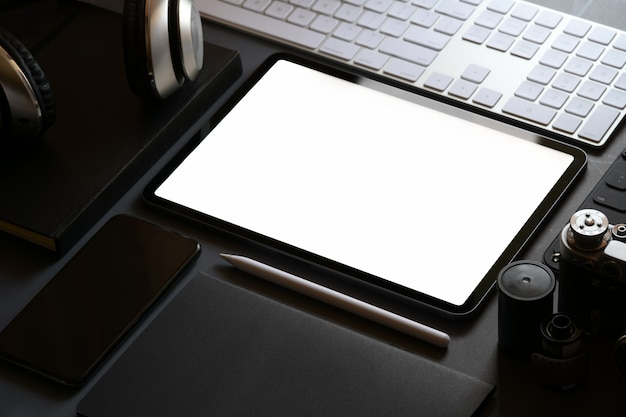 Mockup office stationary with blank screen tablet on dark leather workspace desk Premium Photo
