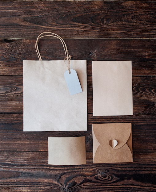 Mockup paper bag from kraft paper with gift tag and christmas gift boxes on a wooden background Premium Photo