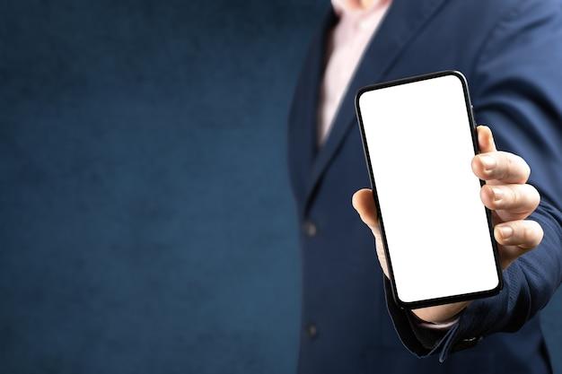모형 전화. 사업가 빈 화면으로 휴대 전화를 보여줍니다. 온라인 비즈니스 개념 프리미엄 사진