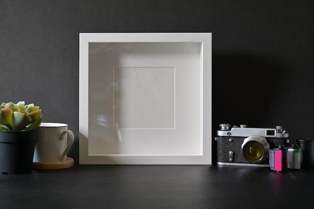 Mockup poster photo frame with vintage film camera on dark leather desk Premium Photo