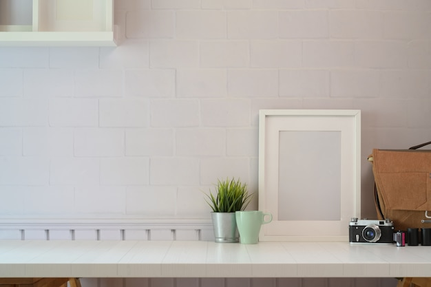 Mockup poster with vantage camera on white wooden desk space and copy space. Premium Photo