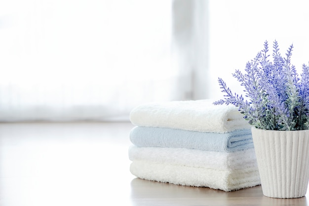 Mockup stack of  towels and houseplant on white table with copy space. Premium Photo