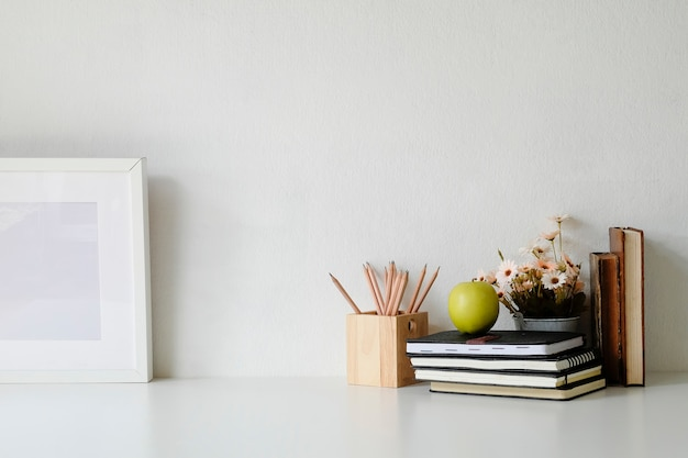 Mockup table with flower, photo frame, books, green apple and jar of pencil on white table. Premium Photo