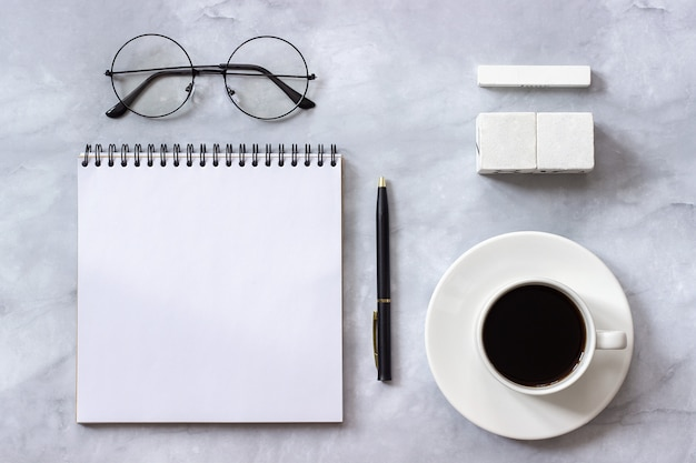Mockup template for calendar date. notepad, coffee, glasses on marble background Premium Photo