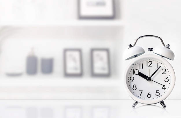 Mockup white alarm clock on white top table in living room. Premium Photo