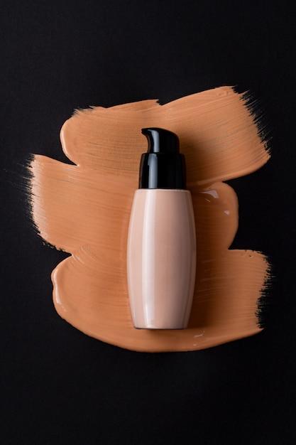 メイクアップフェイスファンデーションボトルと汚れたコンシーラードロップのモックアップ Premium写真