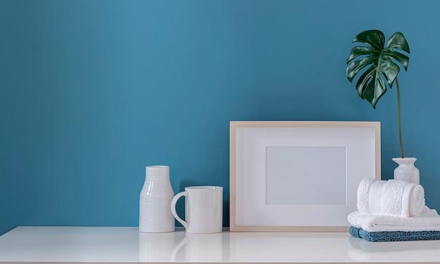 Мокап деревянной рамы с полотенцем и керамической вазой на белом столе Premium Фотографии