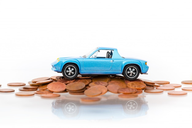Model blue car park on stack golden coins-isolated on white background. Premium Photo