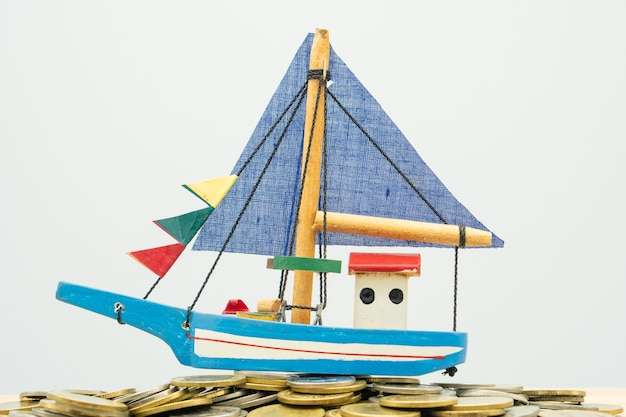 Model boat is placed on a pile of coins.using as background business concept Premium Photo