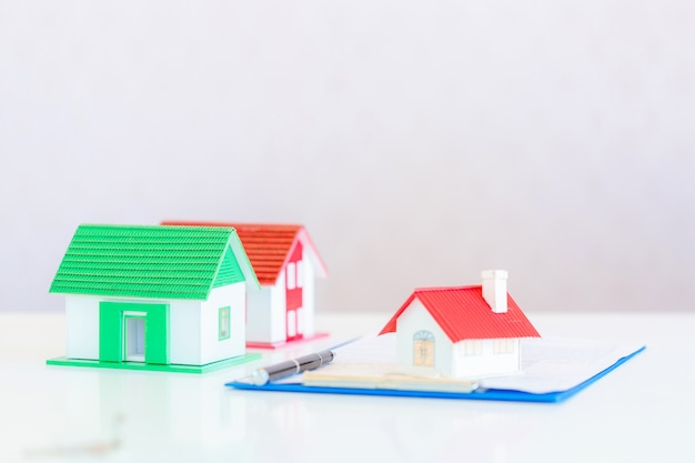 Model of house painted white under the tiled roof on white Free Photo