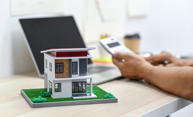 Model house on a table with blurry a person background using calculator and a laptop on the table, real estate expenses. Premium Photo