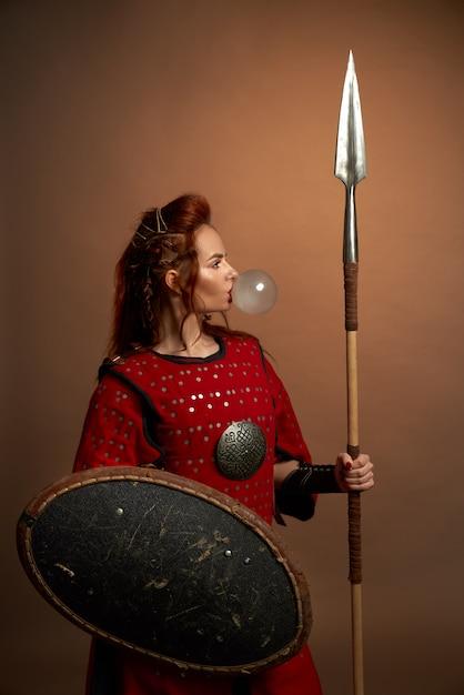 Модель в средневековом костюме позирует, дует жевательная резинка. Бесплатные Фотографии