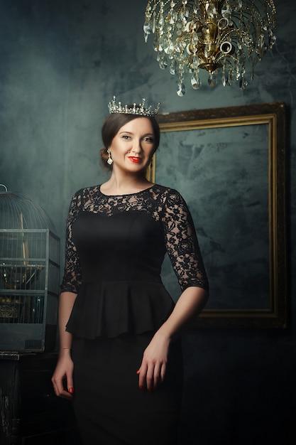 Модель позирует в темной студии как королева Premium Фотографии