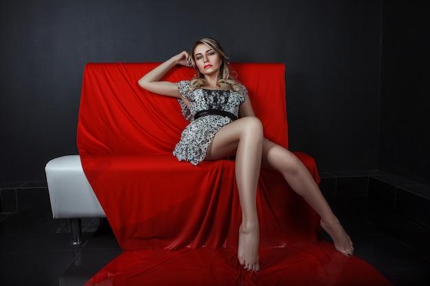 モデルは長い赤い布で暗いスタジオでポーズをとっています Premium写真