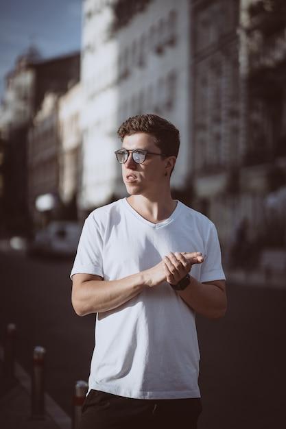 모델 찾고 남자는 도시 거리에 서서 카메라와 주위를 봐 무료 사진