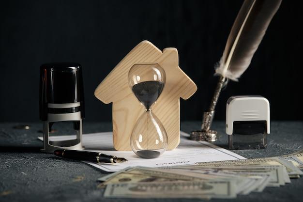 Модель дома, денег и песочных часов. понятие ипотеки или аренды Premium Фотографии