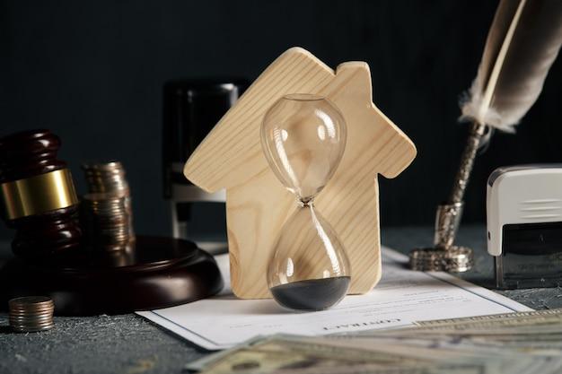 Модель дома, штамп, молоток и песочные часы на столе. домашняя недвижимость и концепция аукциона. Premium Фотографии