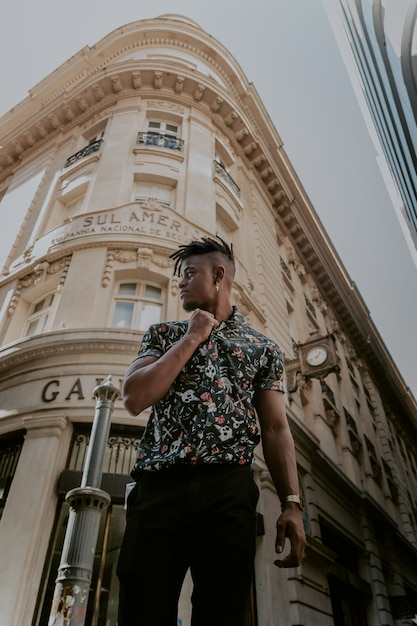 Model in vintage shirt posing in front of a beautiful building Free Photo