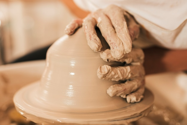 Modeling of clay on a potter's wheel in the pottery workshop Free Photo