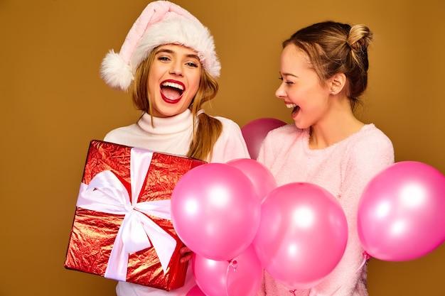 クリスマスに大きなギフトボックスとピンクの風船を持つモデル 無料写真