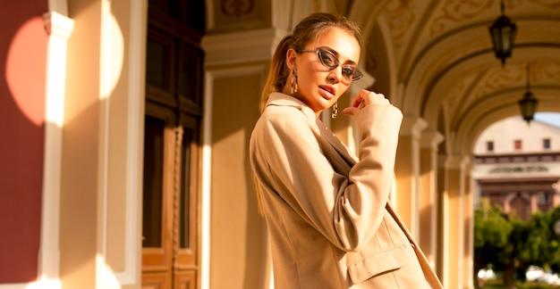 屋外の建物の近くに立っているベージュのコートを着たモダンでかわいい女の子。彼女の顔に華やかなサングラス、メイク、スタイリッシュなテールヘアスタイル。顔の近くの手、たくさんの夏の光、最後の暖かい日 無料写真